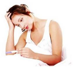 Женщина смотрит на тест беременности