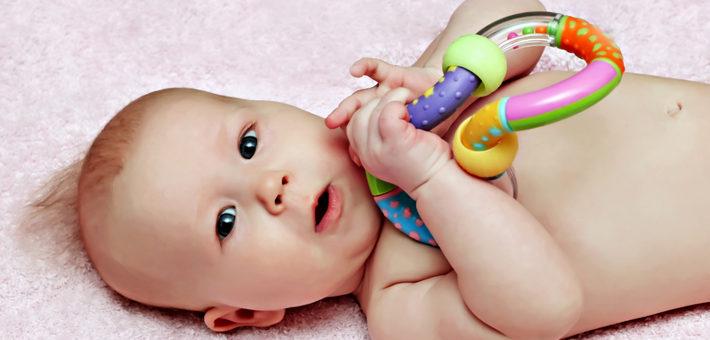 грудничок играет с погремушкой