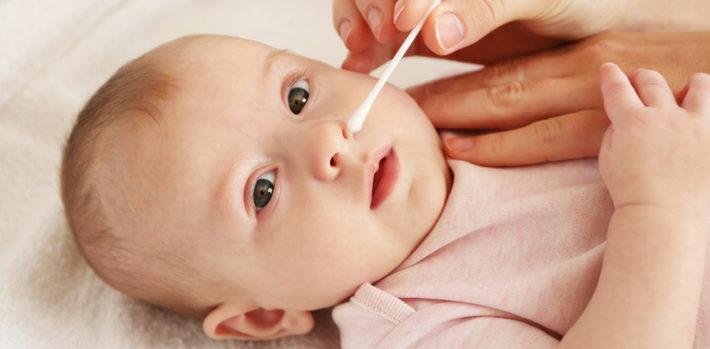 новорожденному чистят носик