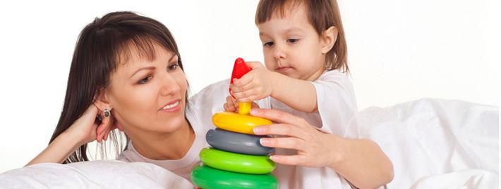 Ребенок играет с пирамидкой рядом с мамой