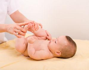 Ребенок лежит на спине задрав ножки кверху