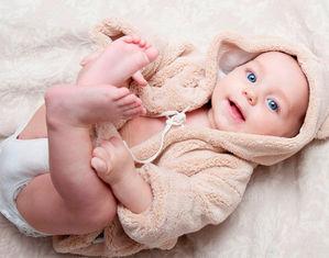 Малыш в халате лежит на спинке