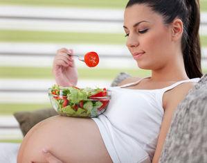 Беременная ест салат у себя на животе
