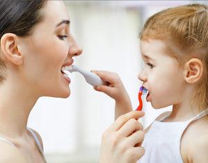 мама с дочерью чистят зубы