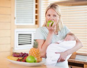Мама с новорожденным ест яблоко