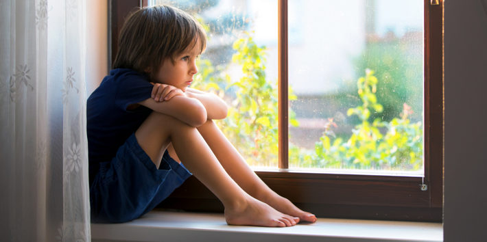 ребенок сидит у окна