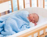 Младенец спит в кроватке