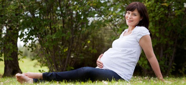 Беременная сидит на траве