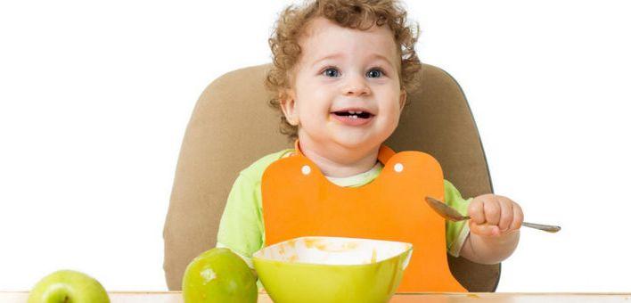 Малыш сидит за столом с ложкой