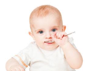 ребенок с ложкой во рту