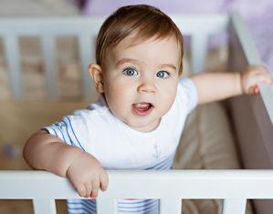 Ребенок стоит в кроватке