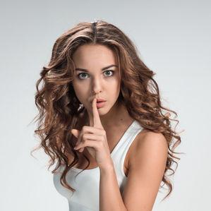 женщина держит палец у рта