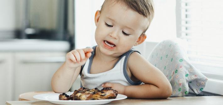 Мальчик сидит перед тарелкой с курицей