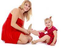 Мама надевает дочке обувь