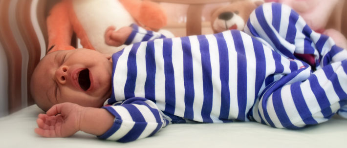 Младенец зевает в кроватке
