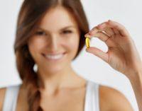 Женщина держит желтую капсулу