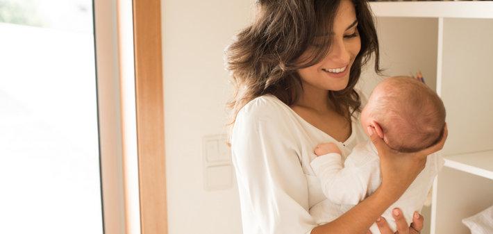 Мама держит младенца и улыбается