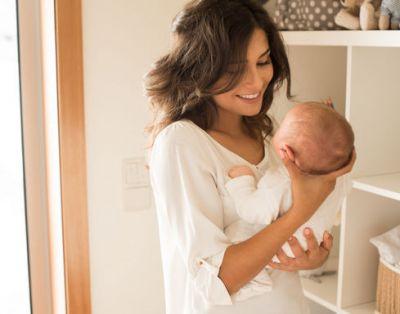 мама держит младенца на руках и улыбается