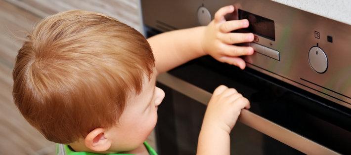 Ребенок стоит у плиты