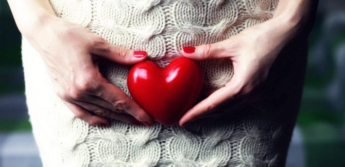 Женщина держит сердечко на животе