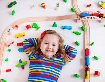 Девочка играет с железной дорогой