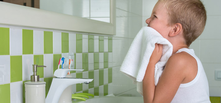 Мальчик вытирается полотенцем