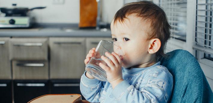 Малыш пьет воду из стакана