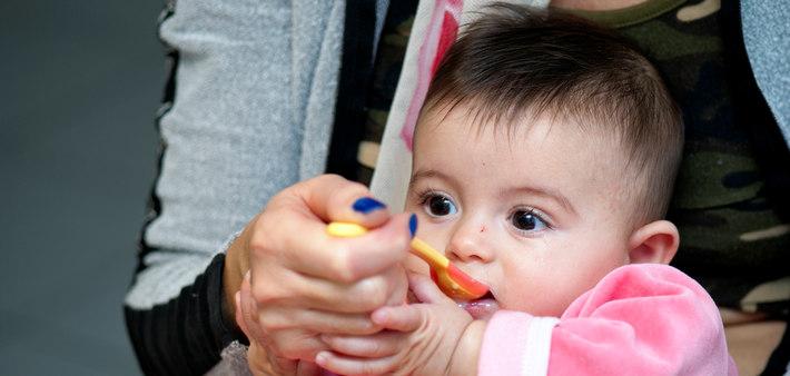 Малыша кормят с ложки