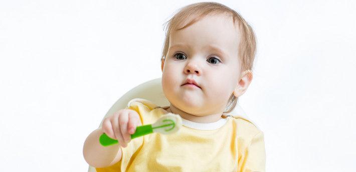 Ребенок за столом с ложкой