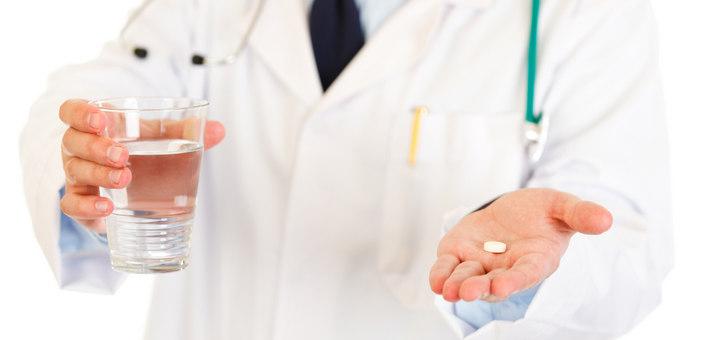 Врач предлагает круглую белую таблетку и стакан воды