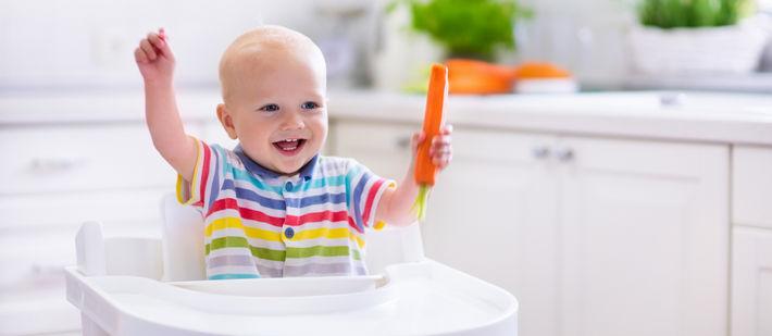 ребенок с морковокой за столом