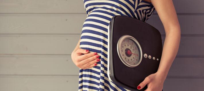 Беременная держит весы