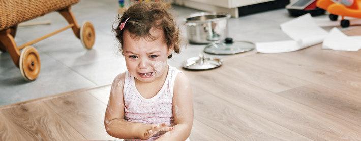 Малышка плачет сидя на полу