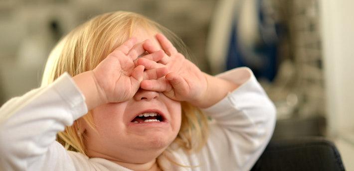 Девочка плачет и закрыла руками лицо