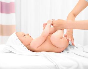 мама смазывает кремом попу грудничку