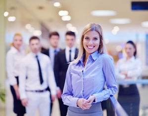 Женщина в офисе на фоне сотрудников