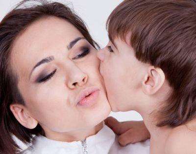 ребенок кусает маму в щеку