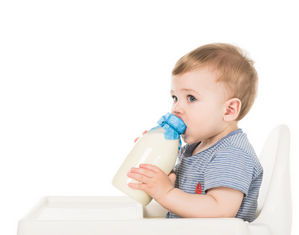 ребенок с бутылкой молока сидит