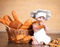 ребенок с хлебом ест бублик