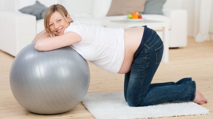 беременная с мячом стоит на коленях