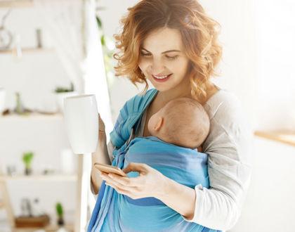 мама пьет чай с ребенком в слинге и улыбается