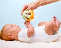 ребенок лежит на спине смотрит на игрушку