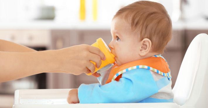 ребенок пьет из поильника с помощью мамы
