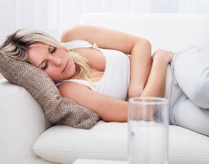 женщина лежит обнимая живот