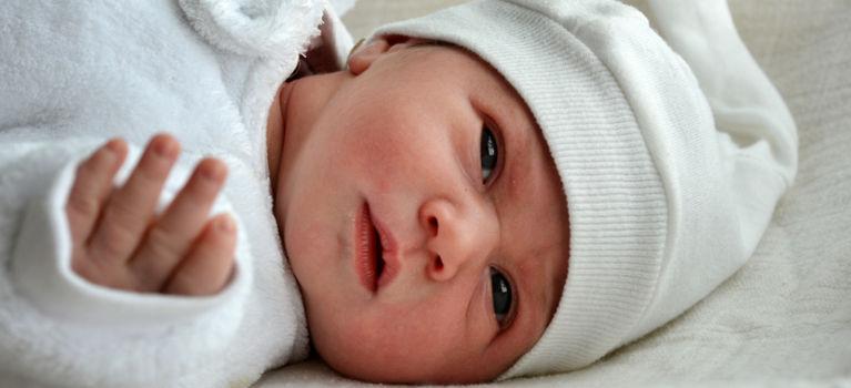 новорожденный лежит на спине в теплой одежде