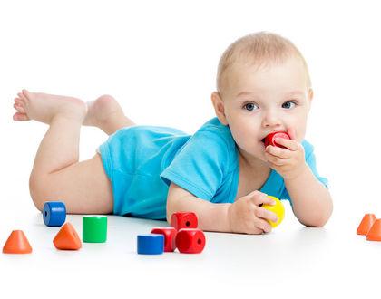 ребенок лежит на животе с игрушкой во рту