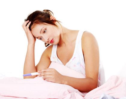 женщина с тестом на беременность задумалась