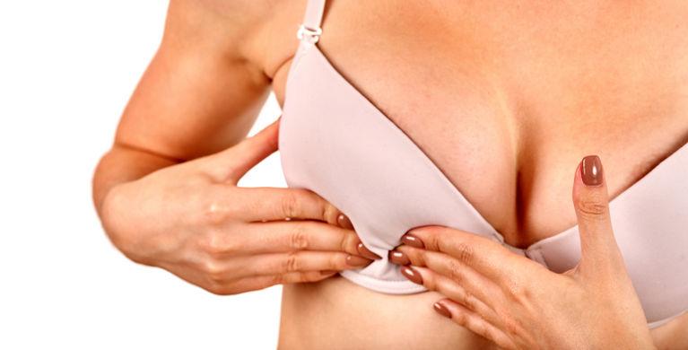 женщина трогает грудь в бюстгальтере