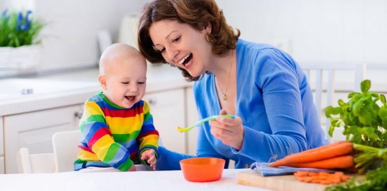мама кормит ребенка и смеется