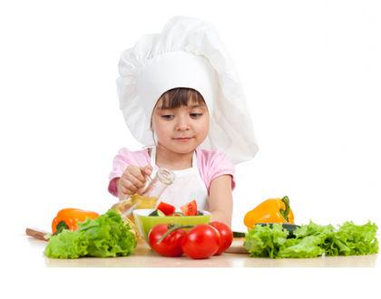 ребенок делает салат из овощей